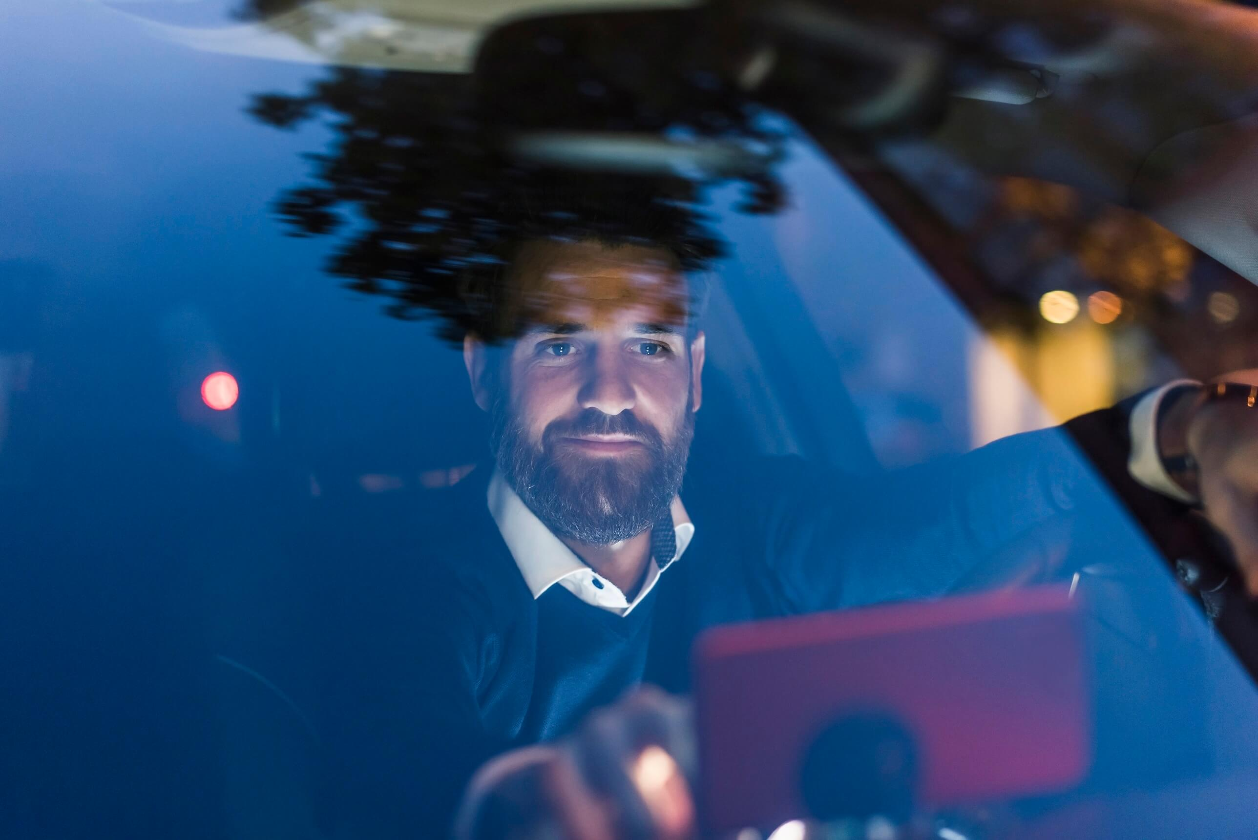 Businessman using navigation device in car at night