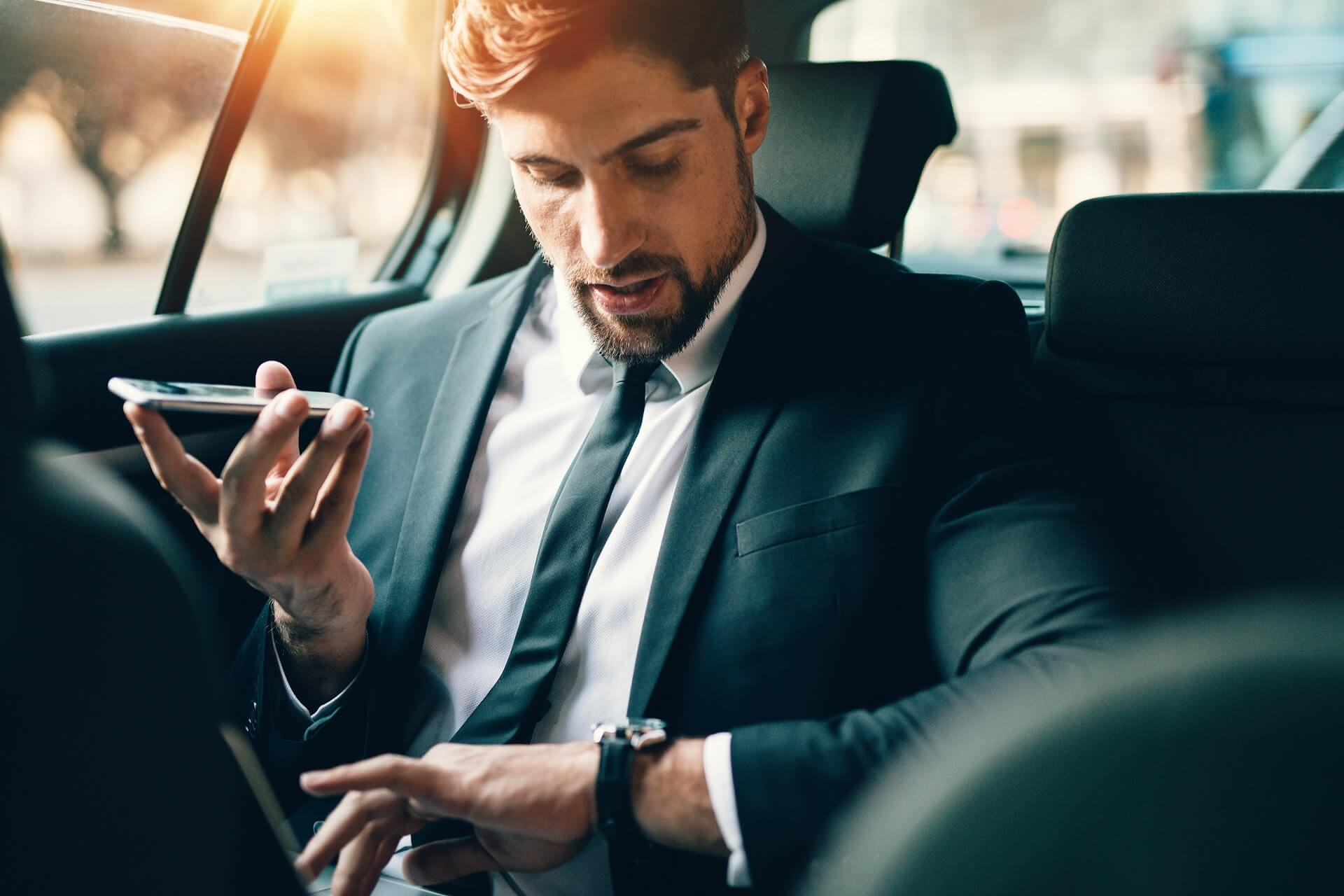 Businessman travelling by car using smart phone and checking time