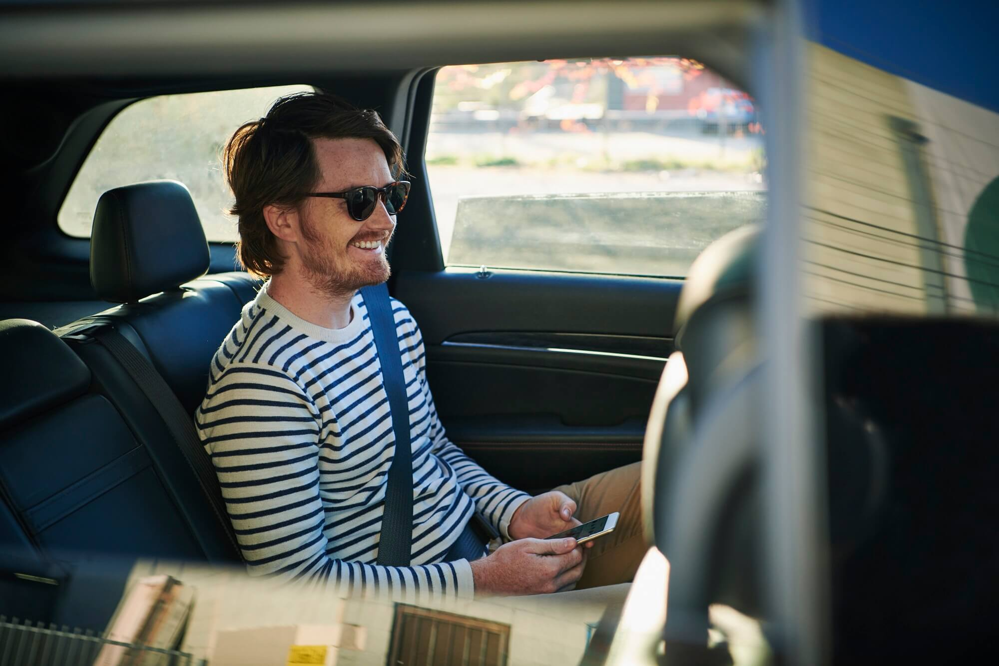 Smiling man with mobile phone sitting in backseat of car