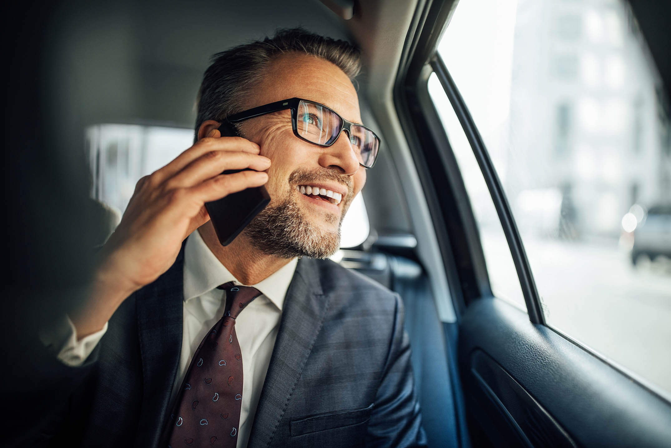 Smiling businessman on cell phone in a taxicab