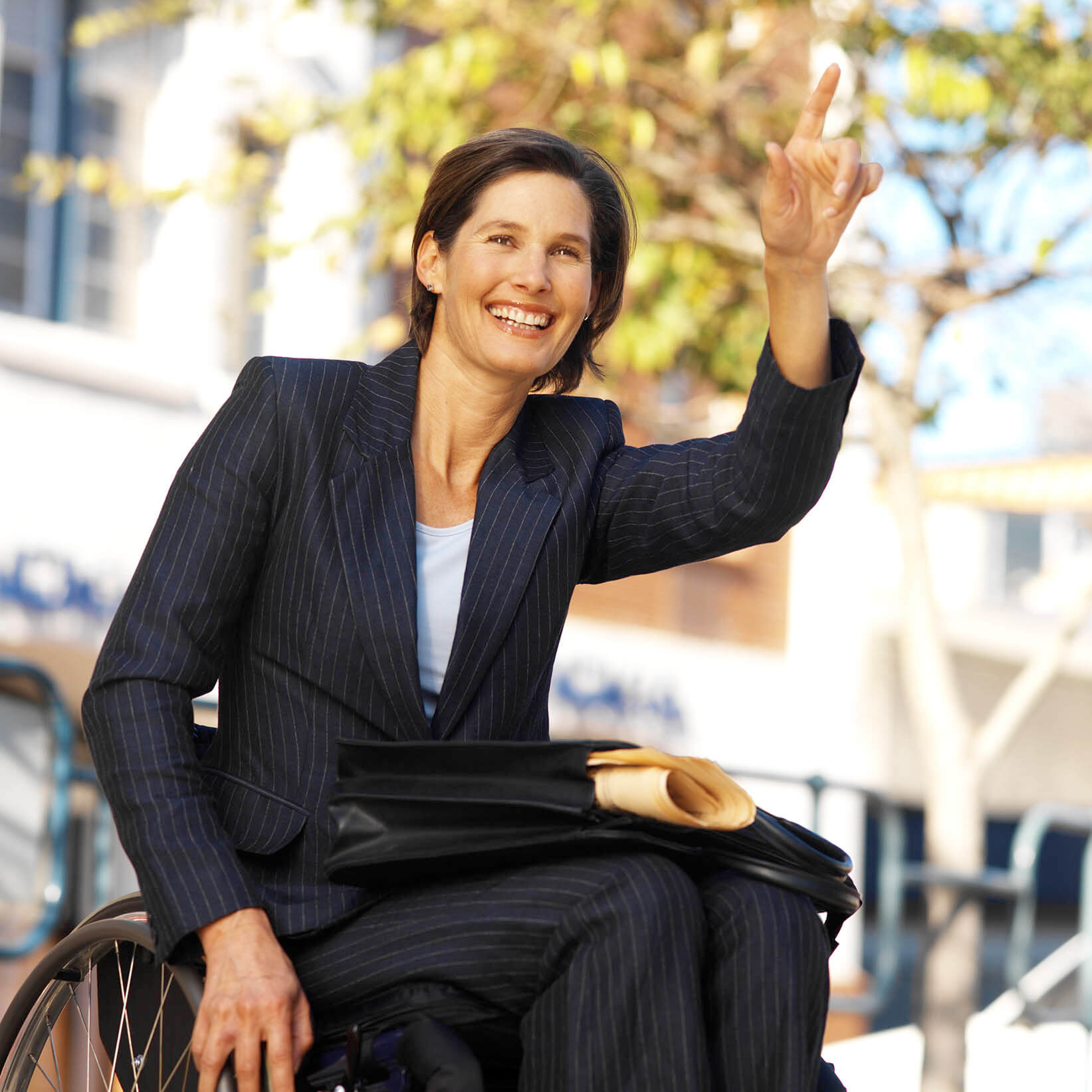 Businesswoman in a wheelchair hailing a taxi